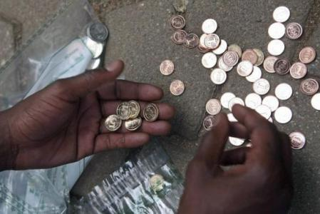 "A Zimbabwean street vendor sorts new coins in front of a bank in Harare, December 18, 2014. Reserve Bank of Zimbabwe governor John Mangudya introduced the new ""bond coins"" in December 2014. REUTERS/Philimon Bulawayo"